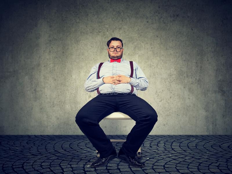 Lazy chunky man sitting on chair stock images