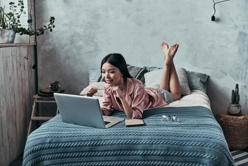 Lazy day at home. Attractive young woman using computer and smiling while lying on the bed at home royalty free stock photography