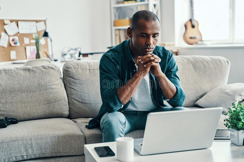 Lazy day at home. Handsome young African man using laptop while sitting indoors royalty free stock photography