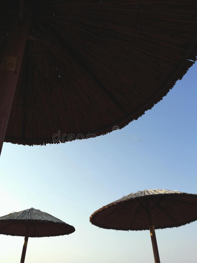 Lazy days. Shade umbrella umbrellas beach sky bamboo friday under three summer time blue lazy days royalty free stock images