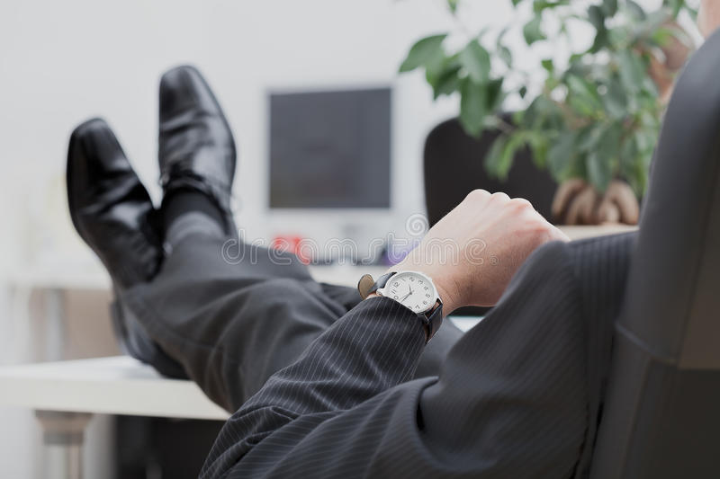 Lazy disrespectful businessman. A lazy businessman sitting disrespectfully with his legs on the desk royalty free stock photo