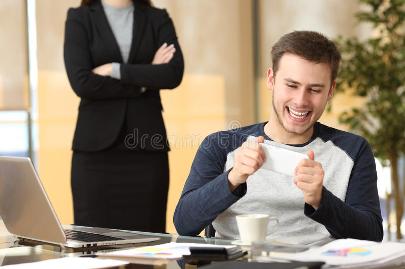 Lazy employee with his angry boss watching stock image