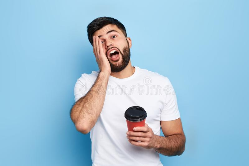 Lazy handsome man yawning, holding a cup of tea, looking at the camera. Close up portrait, isolated blue background, studio shot.laziness concept stock photography
