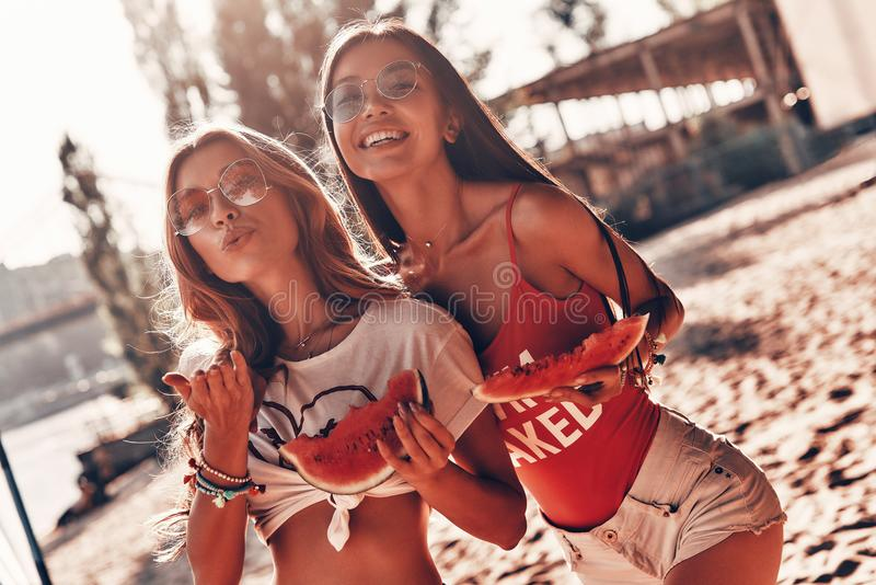 Lazy hot day. Two attractive young women smiling and eating watermelon while standing on the beach royalty free stock images