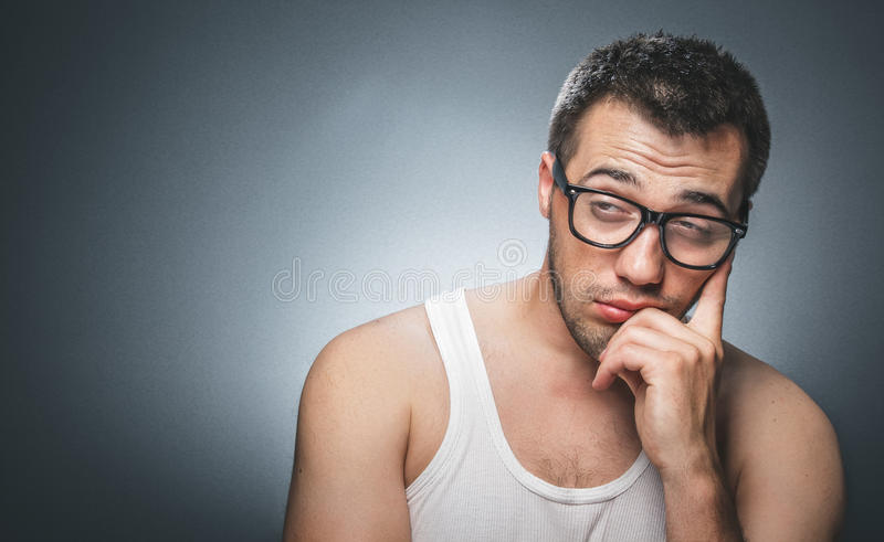 Lazy man. Against gray background. Close up of a tired guy stock images