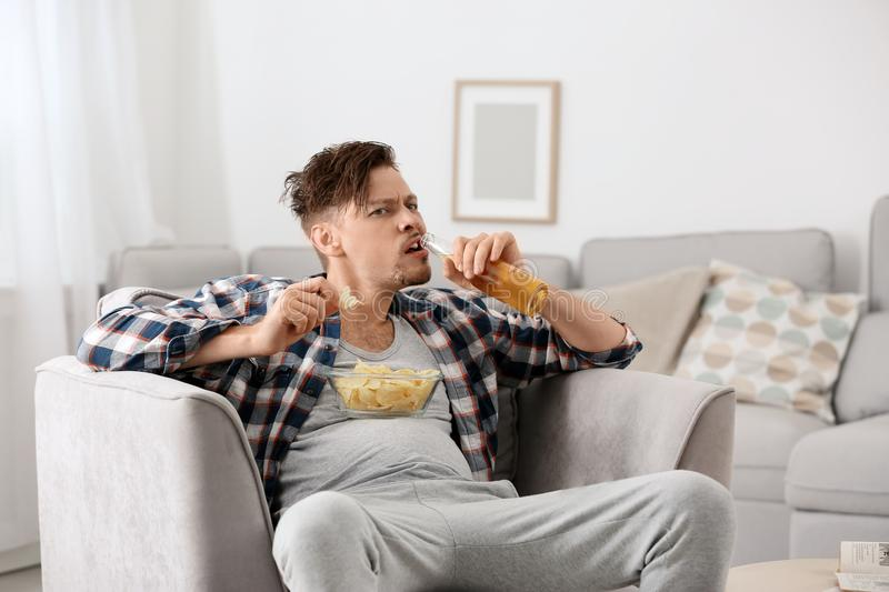 Lazy man with bottle of beer and chips watching TV stock image
