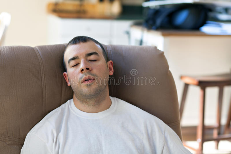Lazy Man Sleeping on the Sofa. Lazy or overtired man sleeping on the couch in the seated position. Shallow depth of field stock photography