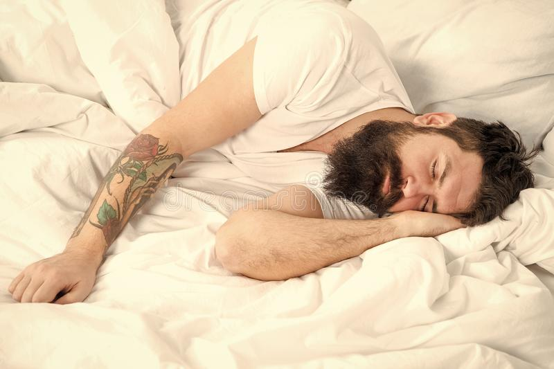 Lazy morning. Man bearded hipster sleepy in bed. Early morning hours. Insomnia and sleep problems. Relax and sleep. Concept. Man bearded guy sleep on white stock images