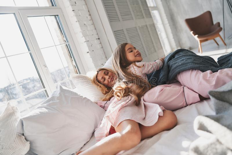 Lazy morning. Mother and daughter spending carefree morning together while lying on the bed at home stock photos