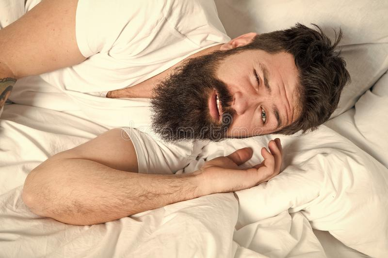 Lazy morning. Relax and sleep concept. Man bearded guy sleep on white sheets. Healthy sleep and wellbeing. Man bearded. Hipster sleepy in bed. Early morning royalty free stock image