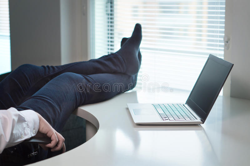 Lazy office worker. With feet and socks on table. Useless and relaxing man doing nothing or taking break from work in workstation. Businessman resting during stock image
