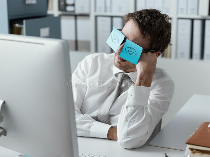 Lazy office worker wearing sticky notes over his glasses stock photo