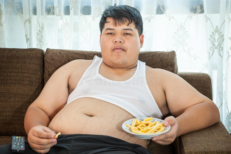 Lazy overweight male sitting with fast food. Lazy overweight asian male sitting with fast food on couch and watching television stock photography