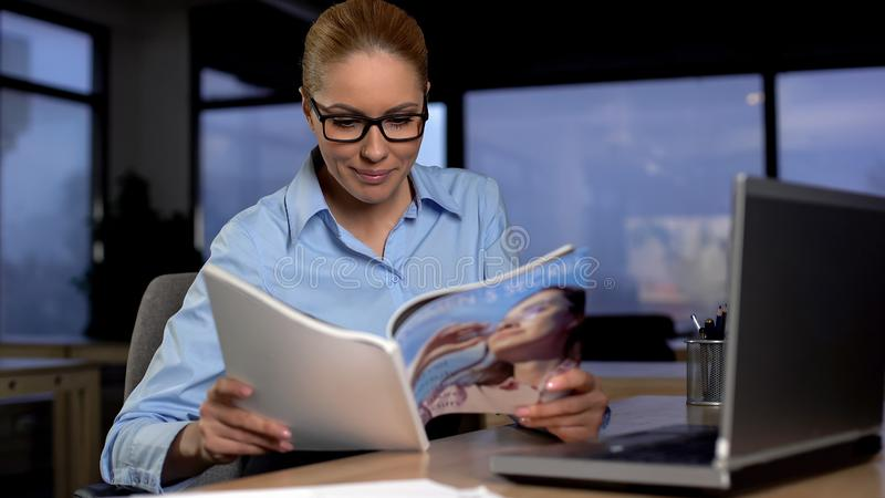 Lazy secretary reading magazine in office, wasting time and avoiding work stock photo