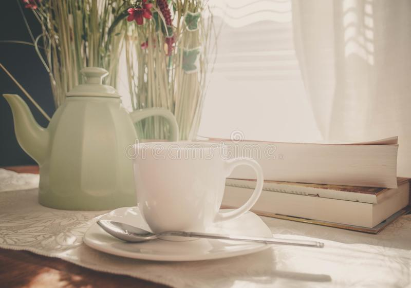 Lazy Sunday mornings. A cup of tea, some flowers, a sunny day, and some good reading. What a perfect Sunday royalty free stock images