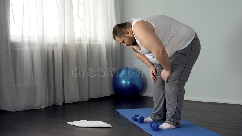 Lazy unmotivated man throwing dumbbells on floor, hopelessness, insecurities royalty free stock photos