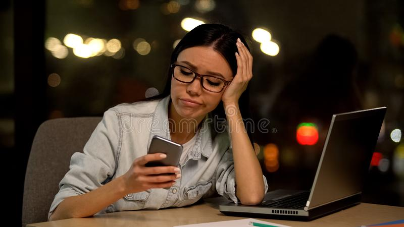 Lazy woman using cell phone at workplace, avoiding boring job, distraction stock photos
