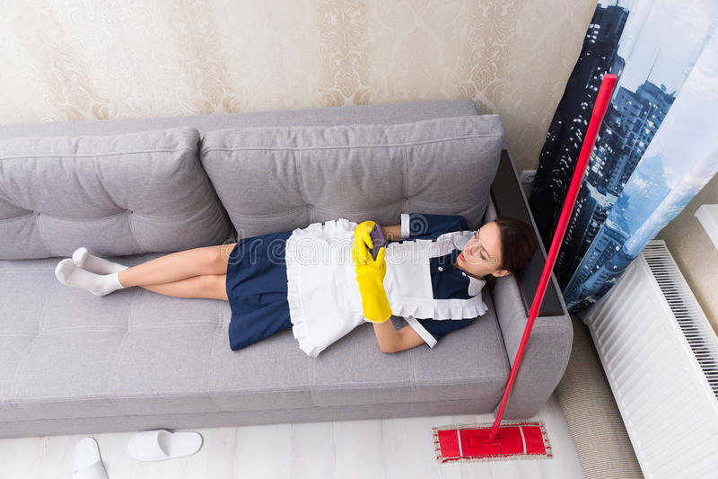 Lazy work shy housekeeper taking a break. Lazy work shy housekeeper in uniform taking a break lying on her back on a sofa with her mop beside her checking her royalty free stock photo