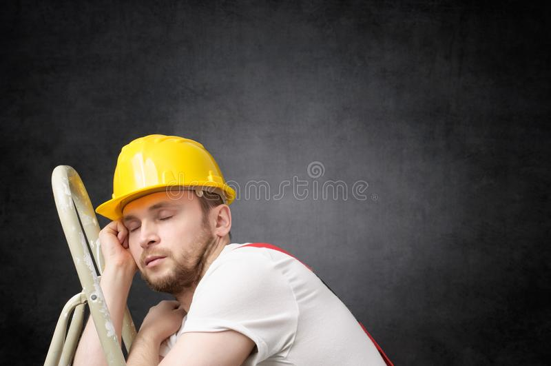 Lazy worker with ladder. Lazy construction worker sleeping on a ladder stock photo