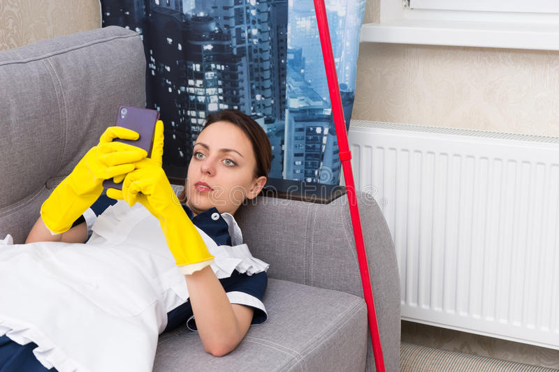 Lazy young housekeeper or maid relaxing on a sofa royalty free stock photo