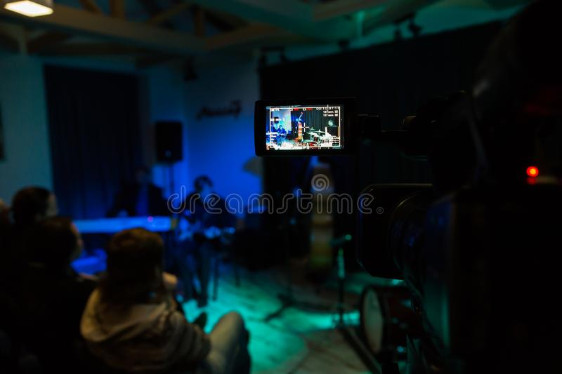 LCD display on the camcorder. Filming of the concert. Musicians playing the double bass, synthesizer, guitar and percussion stock images