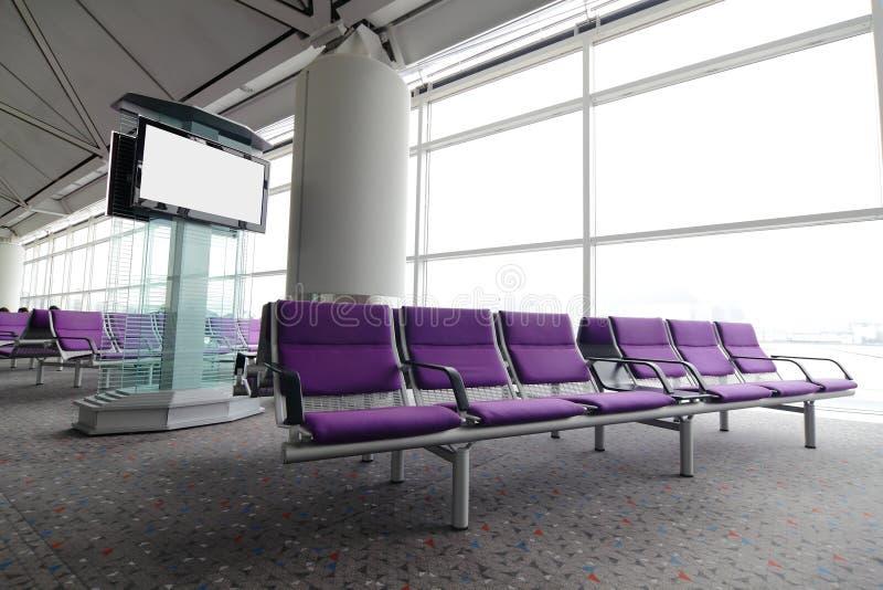 Lcd-Fernsehapparat und Reihe des purpurroten Stuhls am Flughafen stockfoto