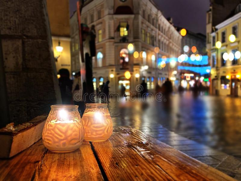 Holiday season night street cafe wooden table top with two candle cup , city night  in Tallinn ,street blurred light old  town tra. Vel  in Estonia Europe night royalty free stock photo