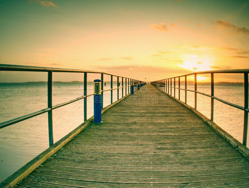 lDaybreak ranku drewniany dok & x28; pier& x29; pomarańczowy morze i jasny niebo fotografia royalty free