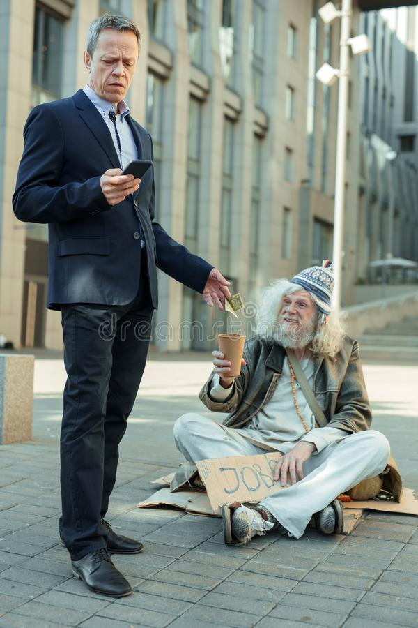 Lderly rich businessman giving some money to poor man stock images