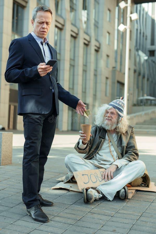 Lderly rik affärsman som ger några pengar till den fattiga mannen arkivbilder