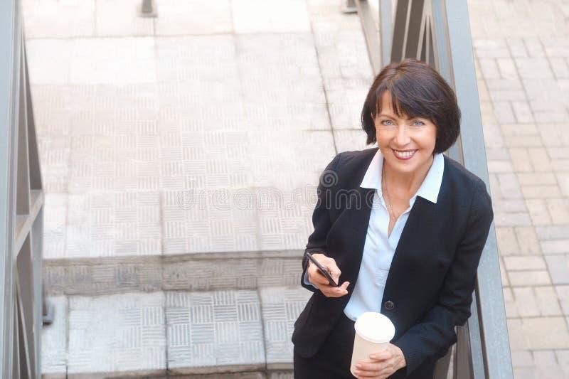 ?ldre aff?rskvinna med kaffe, genom att anv?nda mobiltelefonen som ?r utomhus- royaltyfri fotografi