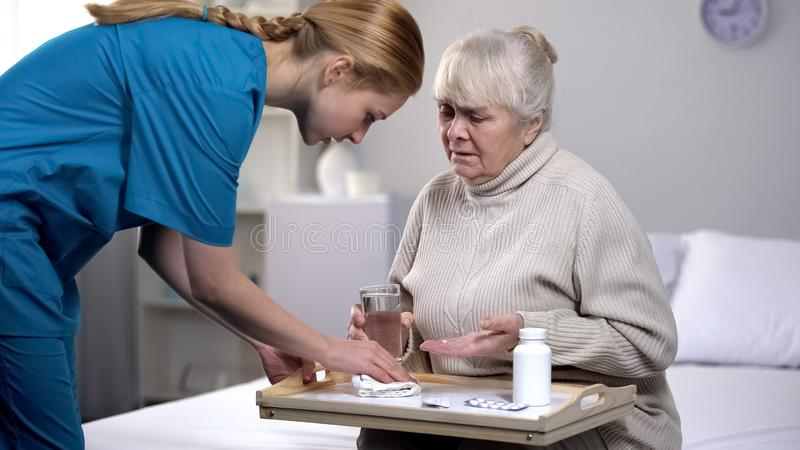 ?ldre kvinnlig patient som spiller vatten p? magasinet, medan ta piller, d?lig service arkivfoton