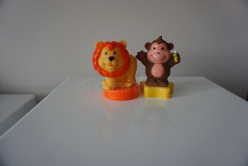 Leão alaranjado e brinquedos marrons do plástico do macaco foto de stock royalty free