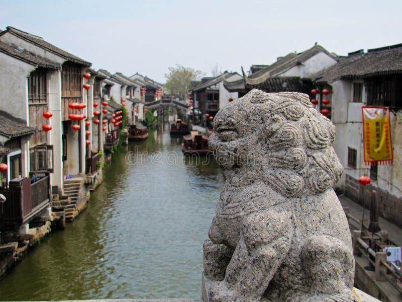 Leão de pedra em uma ponte sobre um canal de água em Suzhou fotos de stock royalty free