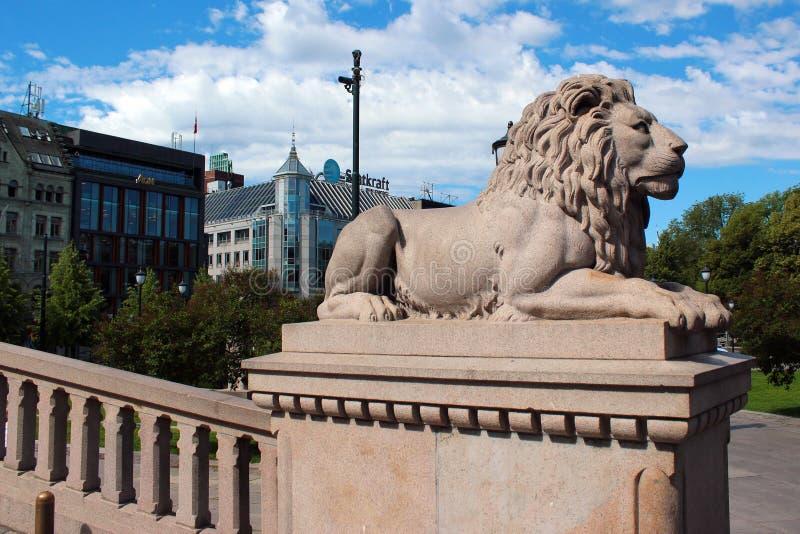 Leão de pedra na frente do Storting em Oslo, Noruega - 26 de junho de 2018: Teatro nacional em Oslo, Noruega fotografia de stock