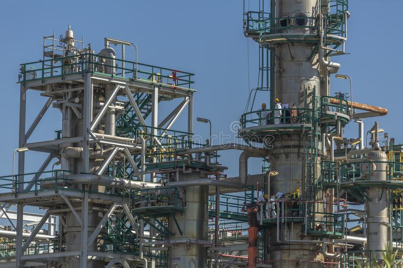 View at the industrial complex of oil refinery and people working in, with buildings, equipment and machinery, blue sky background stock images