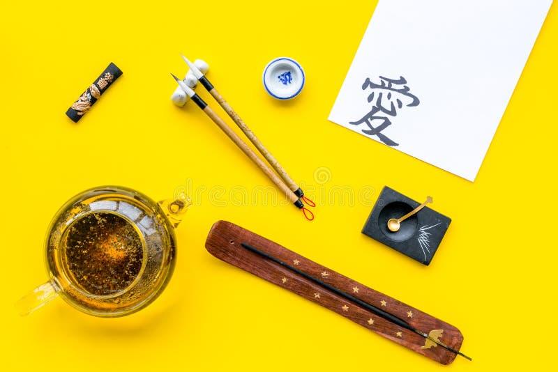 Leçon de concept de calligraphie Papier avec l'hiéroglyphe près d'écrire les accessoires, la théière et la tasse de thé sur le ja photos stock