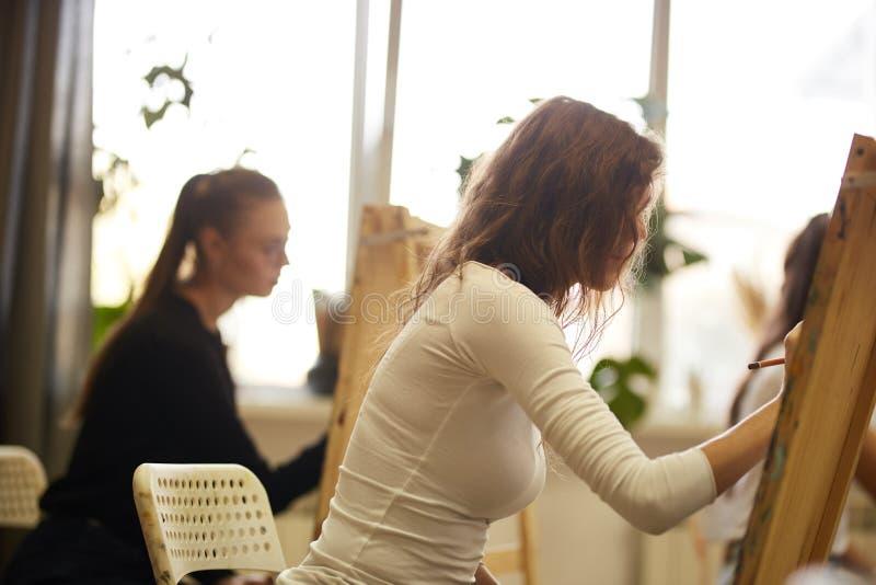 Le?on de dessin dans le studio d'art Les filles peignent des tableaux se reposant aux chevalets images libres de droits