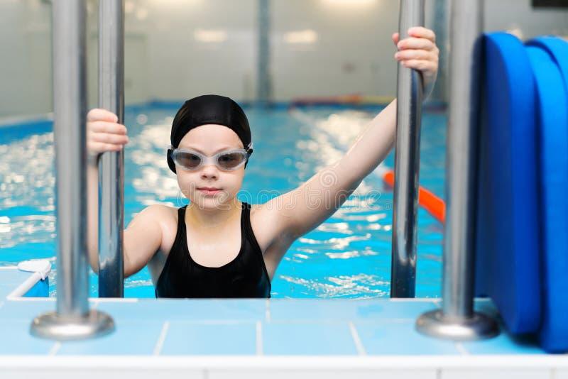 Leçons de natation pour des enfants dans la piscine - la belle fille blanche nage dans l'eau images stock