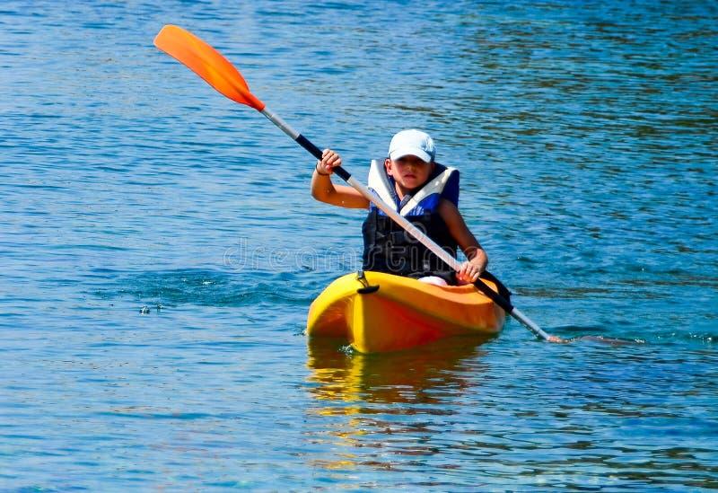 Leçons Kayaking Garçon avec le costume de balise de vie dans le duri de leçons de kayak images libres de droits