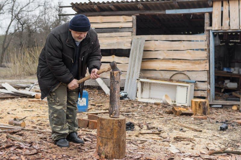 Leña choping del viejo campesino ucraniano fotos de archivo libres de regalías