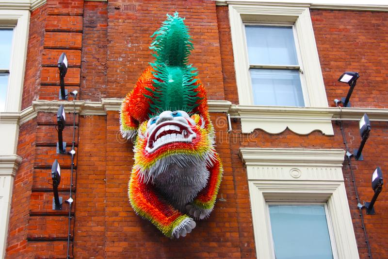 León chino o dragón colorido en la pared de ladrillo roja en Chinatown en Soho Londres central para las celebraciones del Año Nue fotografía de archivo libre de regalías
