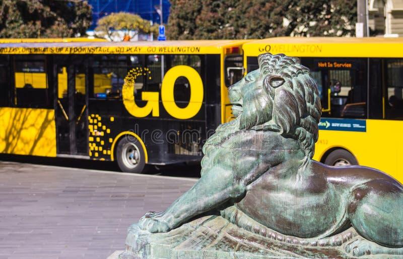 León de bronce en la base de Wellington Cenotaph con los autobuses de la ciudad en el fondo imagen de archivo