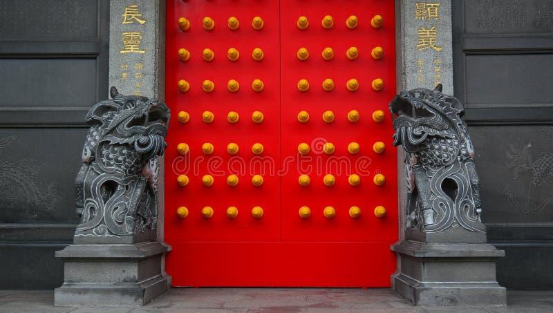 León de piedra chino en el templo con la puerta roja imagenes de archivo
