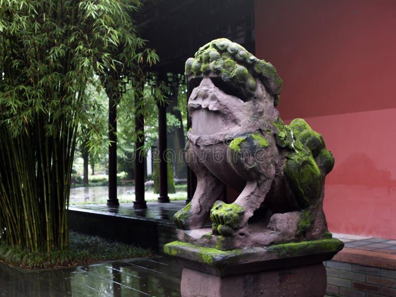 León de piedra cubierto de musgo delante de un edificio chino foto de archivo