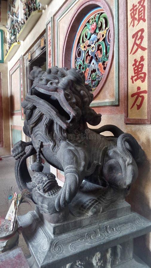 León viejo de Bronz el guarda de una capilla china en la comunidad de Tarad Noi en lado del río de Chaopraya en Bangkok imagen de archivo