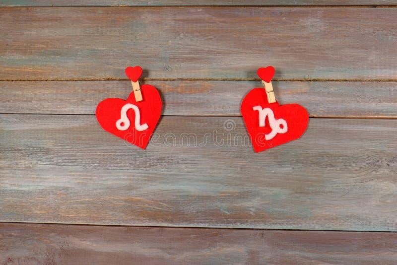 León y Capricornio muestras del zodiaco y del corazón Backgr de madera foto de archivo