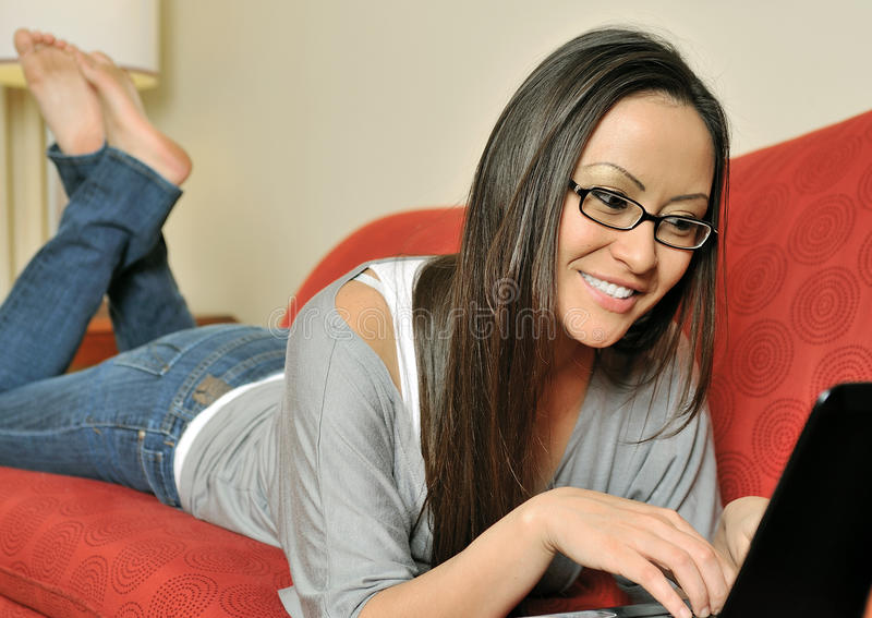 Leżanka kobieta używać laptop na leżance obraz stock