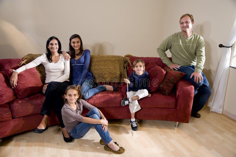 leżanki rodziny pięć międzyrasowy żywy pokój zdjęcie stock
