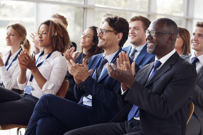 Le åhörare som applåderar på ett affärsseminarium royaltyfri foto